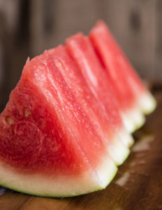Sliced juicy watermelon on wooden chopping board in kitchen